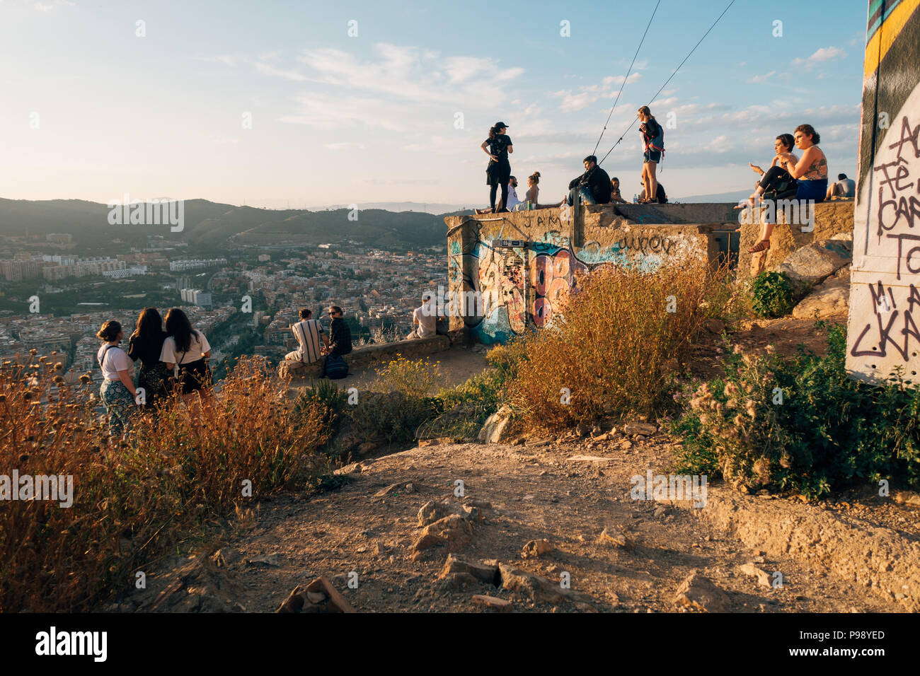 a young group of tourists sit atop Bunquers del Carmel at sunset, a famous lookout over the city of Barcelona, Spain Stock Photo