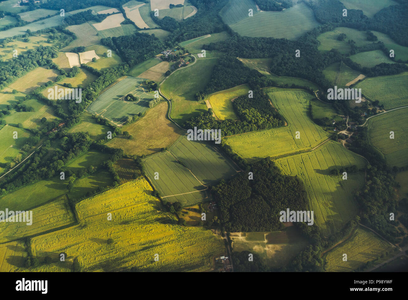 patches of grassy green British farmland seen while flying into the United Kingdom Stock Photo