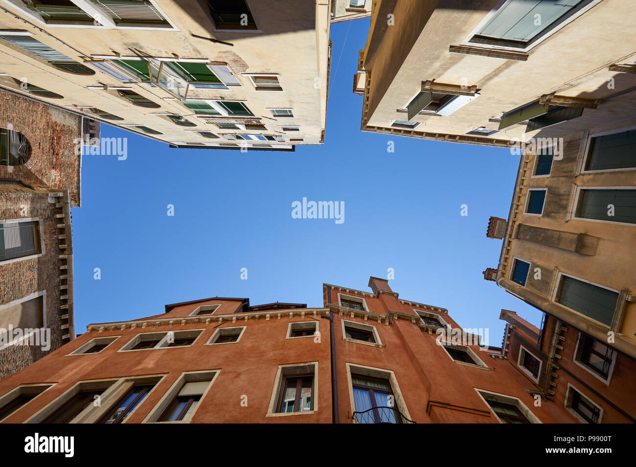 Venice buildings and houses facades low angle view in a sunny day, blue sky in Italy - Stock Image
