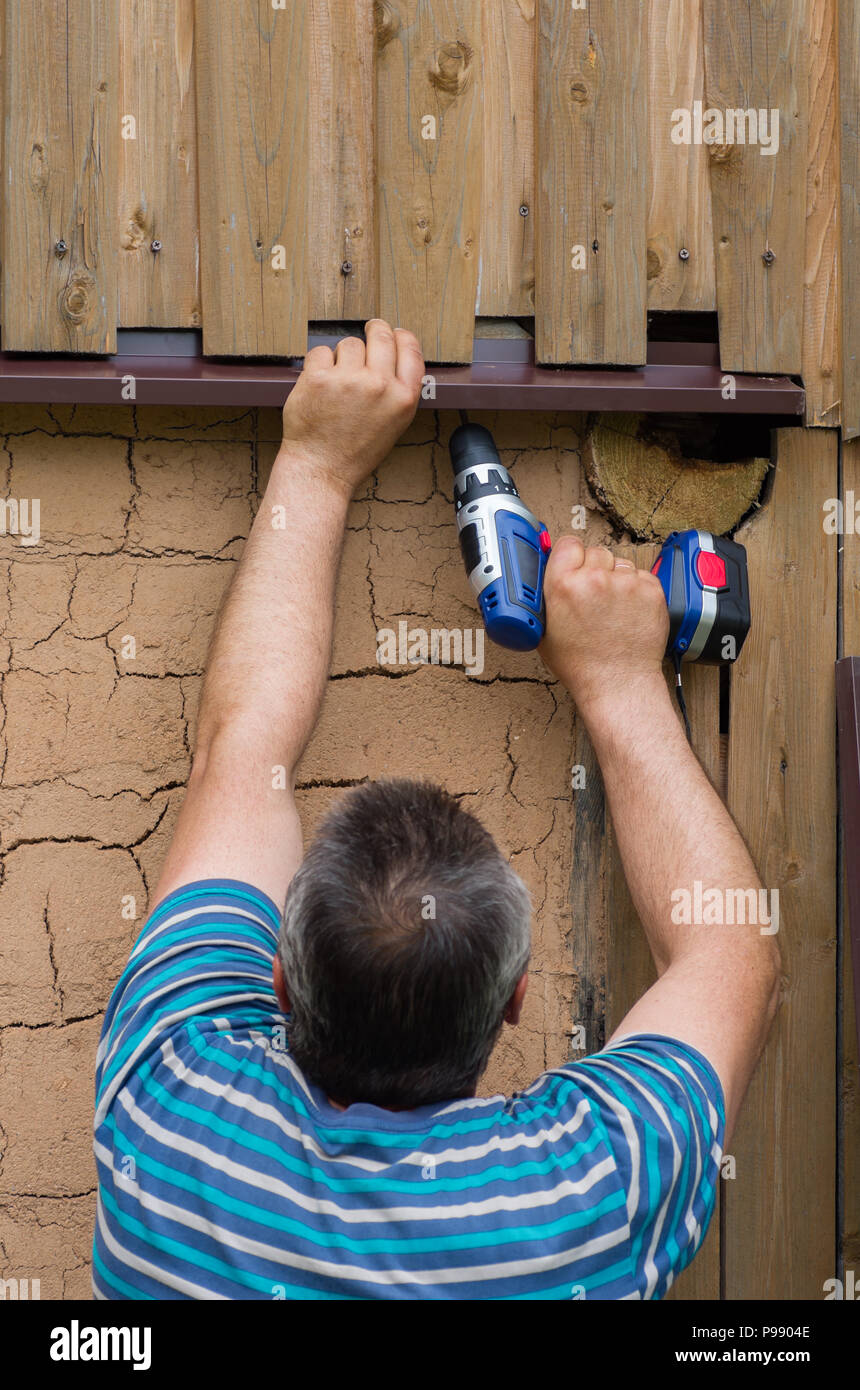 The person is engaged in construction with the help of an electric screwdriver - works on the spot with the help of a hand tool. Construction works. - Stock Image