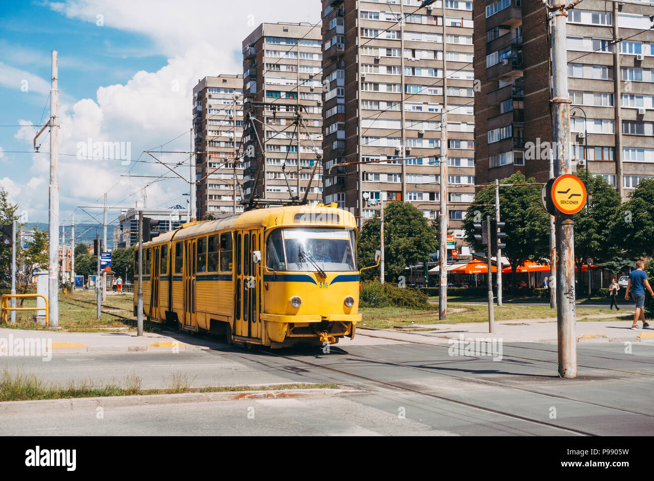 a yellow Tatra T3 tramcar crosses the road on the outskirts of Sarajevo, Bosnia and Herzegovina - Stock Image