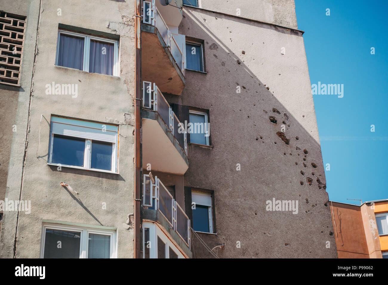 Holes from shell shrapnel still marks the walls of many buildings and homes in Sarajevo, Bosnia and Herzegovina, decades after the seige ended - Stock Image