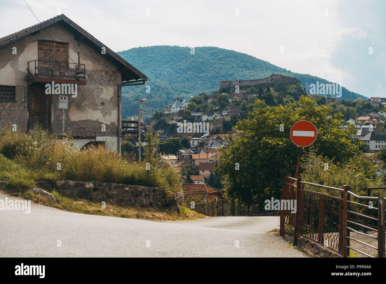 a quaint little countryside house in the small town of Jajce, Bosnia and Herzegovina. The fort can be seen on the hill behind Stock Photo