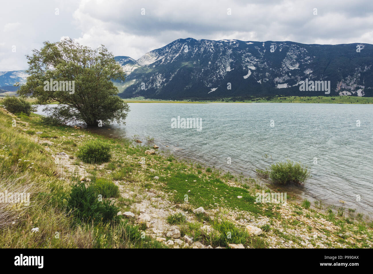 An overcast day next to the calm waters of Blidinje Jezero, the largest lake Bosnia and Herzegovina - Stock Image