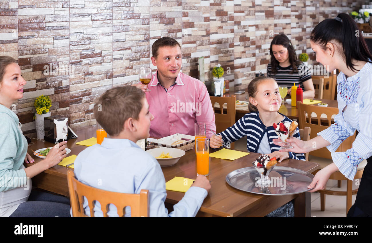professional brunette waitress serving cheerful family in comfy family cafe - Stock Image