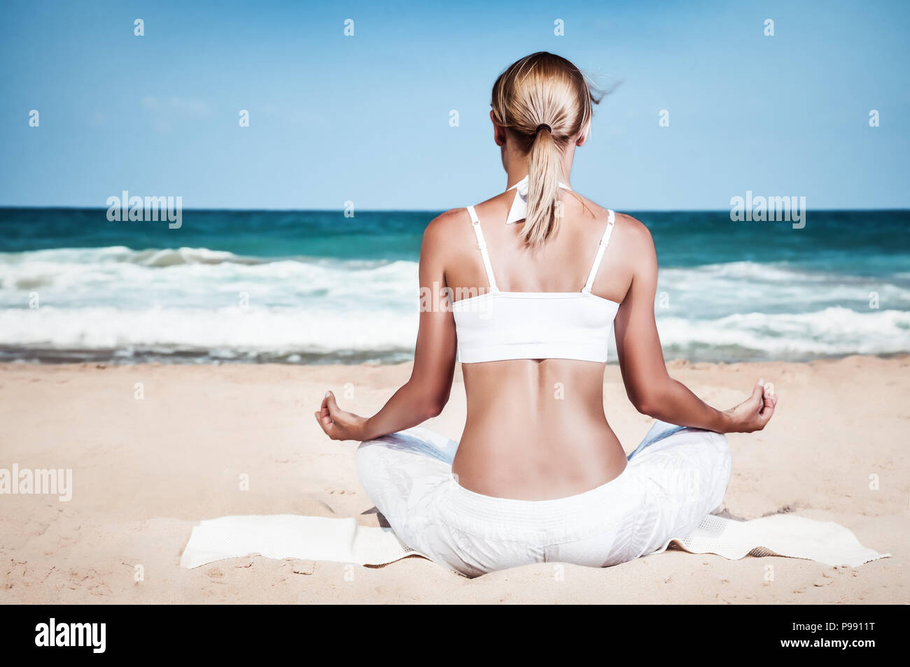 Woman meditating on the beach, rear view of a slim healthy girl sitting in lotus pose and enjoying beautiful view of a sea, mindfulness - Stock Image