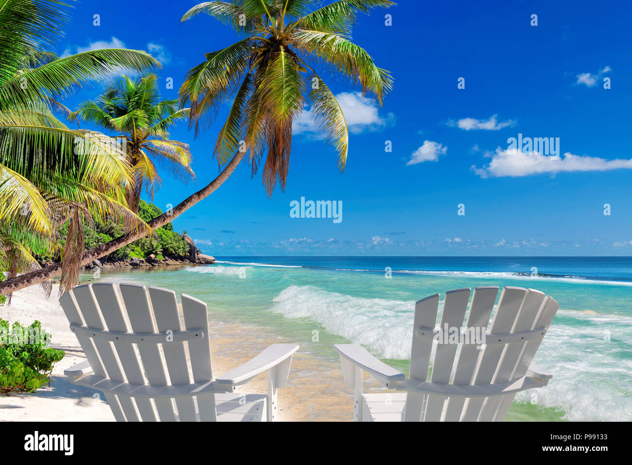 Beach chairs on sandy beach with palm and turquoise sea. - Stock Image