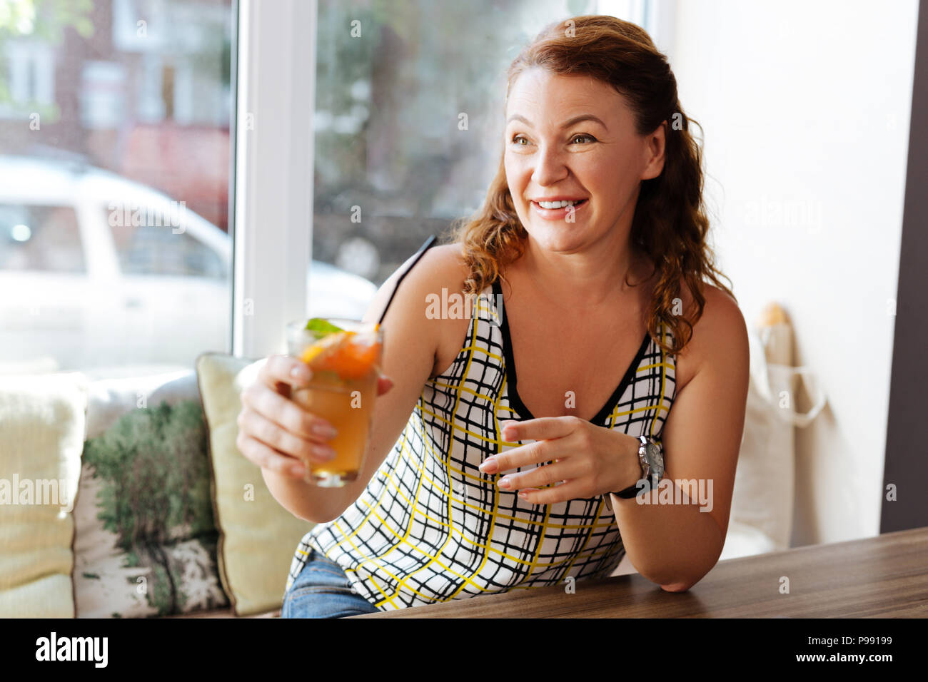 Red-haired beaming woman drinking cocktail in restaurant - Stock Image