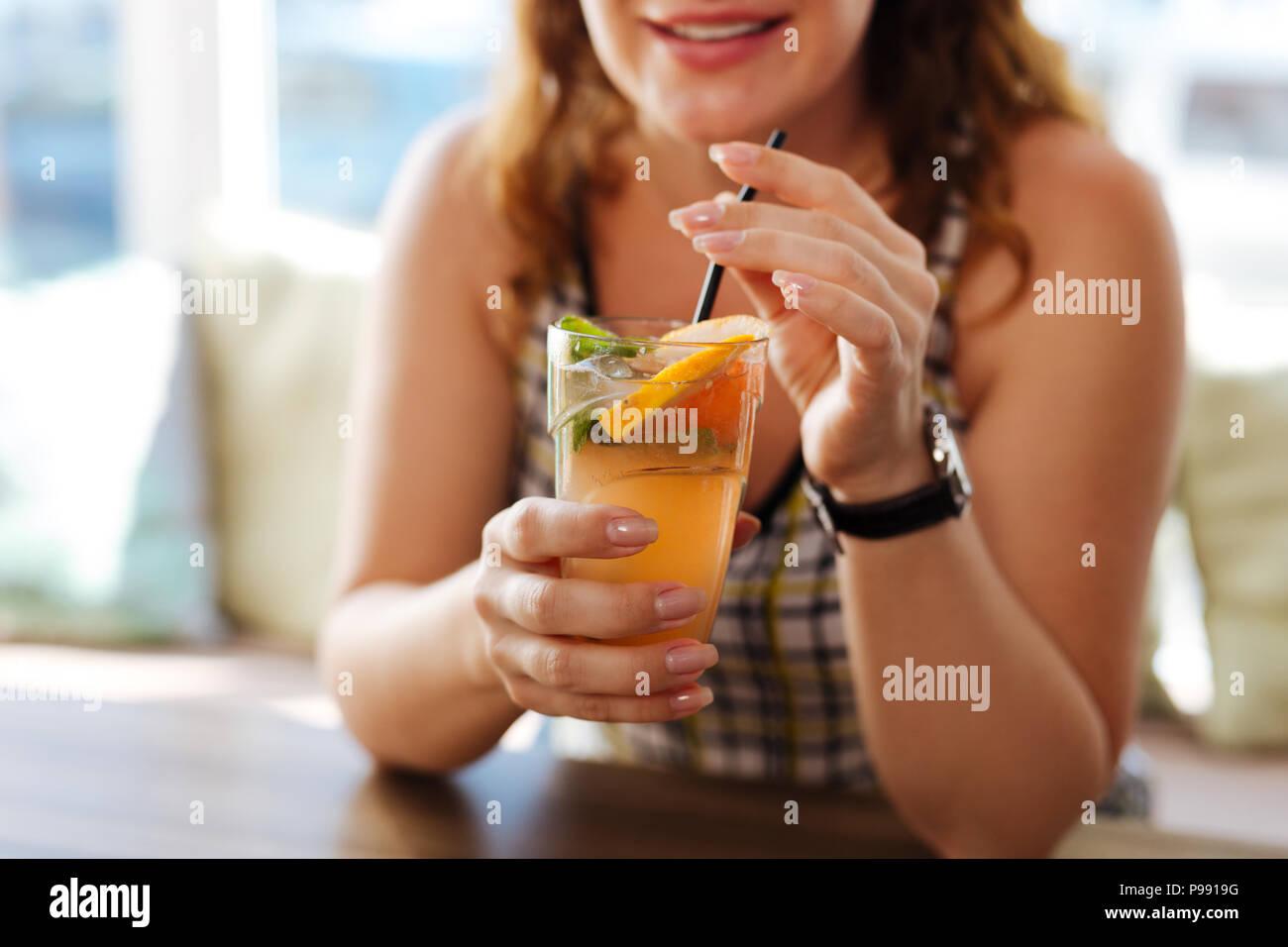 Stylish beautiful woman enjoying her cold cocktail - Stock Image