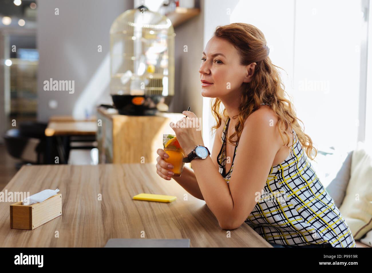 Beautiful woman with wavy hair waiting for her man - Stock Image