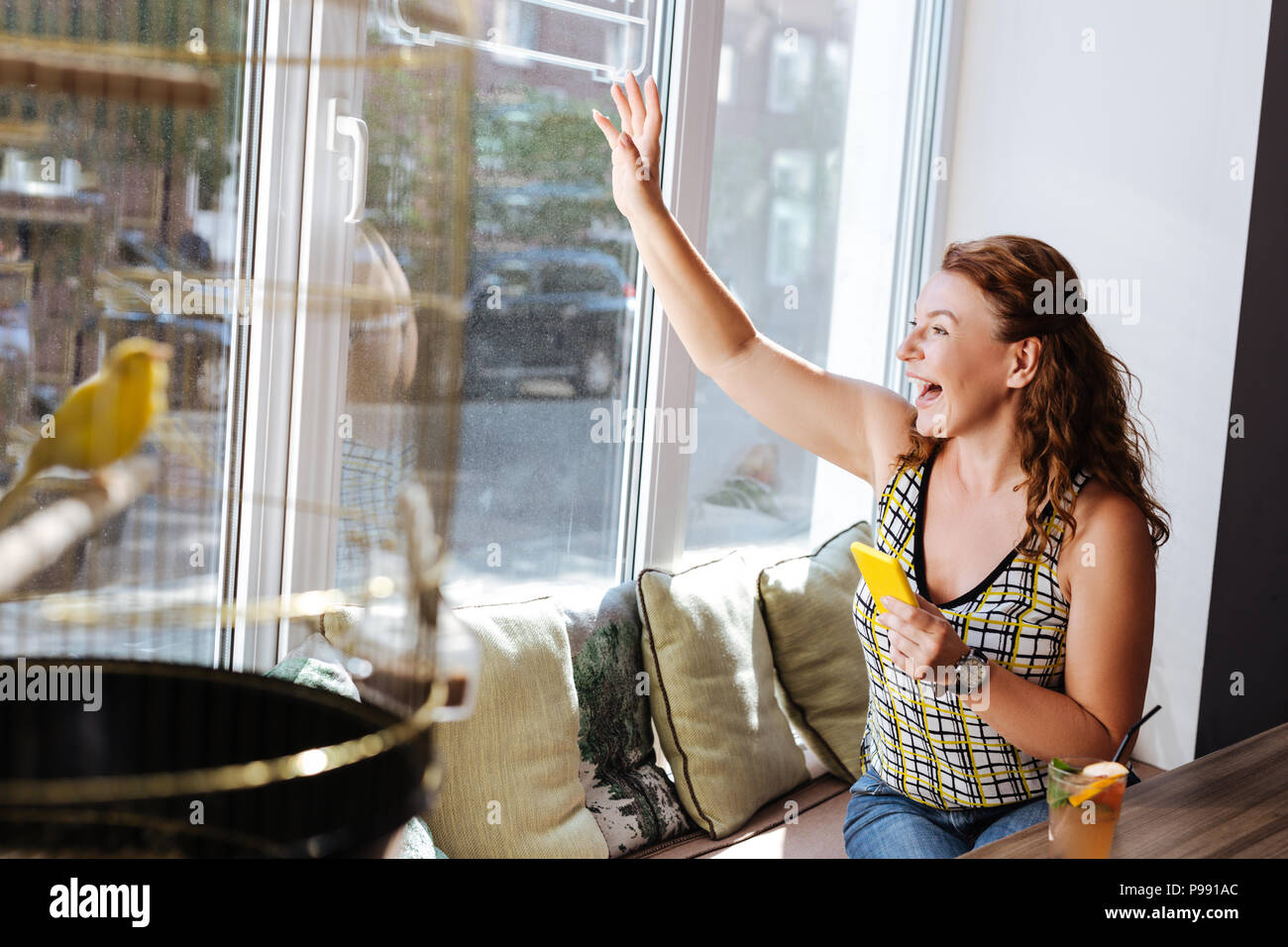 Happy woman seeing her old friend while sitting in cafe - Stock Image