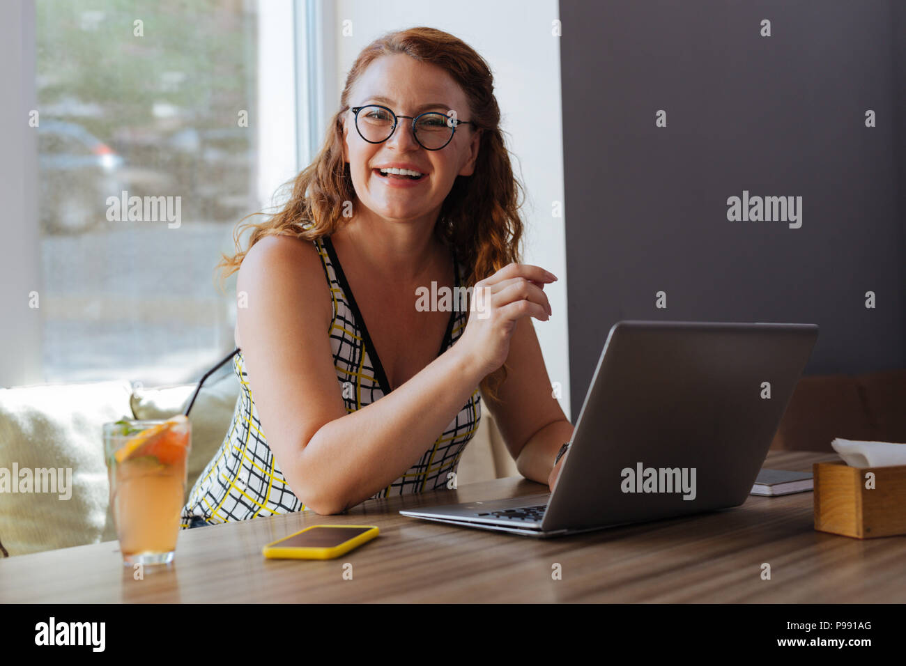 Dark-haired remote worker using her laptop - Stock Image