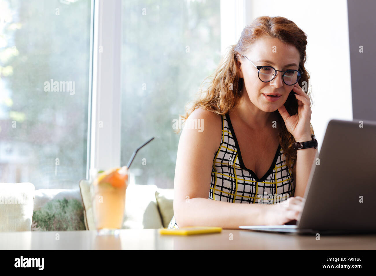 Freelance worker calling her husband while working from cafe - Stock Image