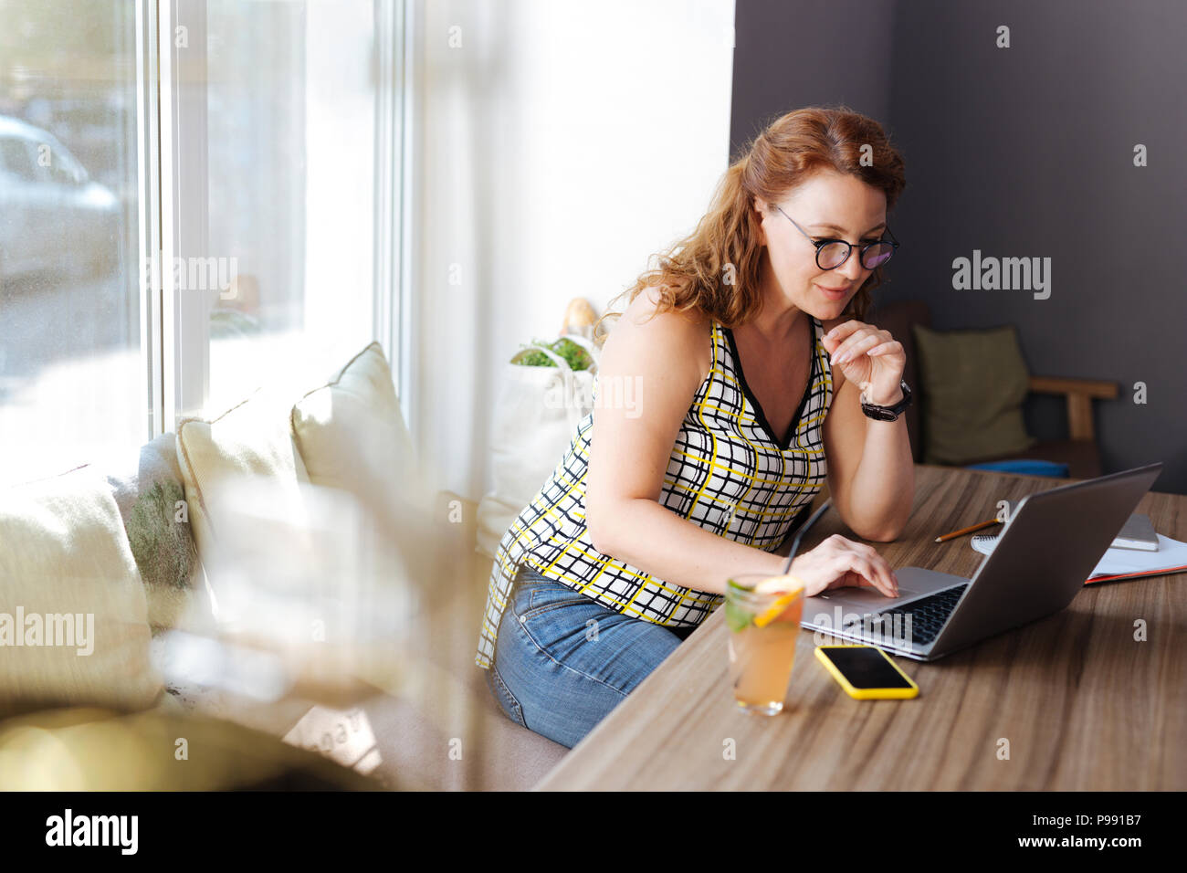 Red-haired freelance writer sitting in cafe while working hard - Stock Image