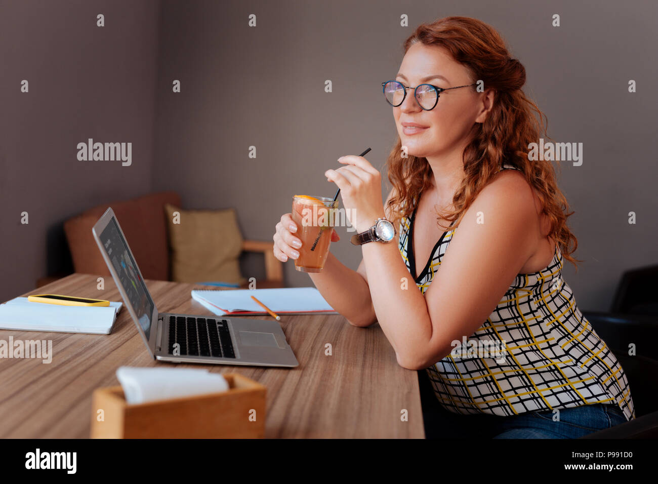 Appealing mature woman wearing glasses drinking cold cocktail - Stock Image
