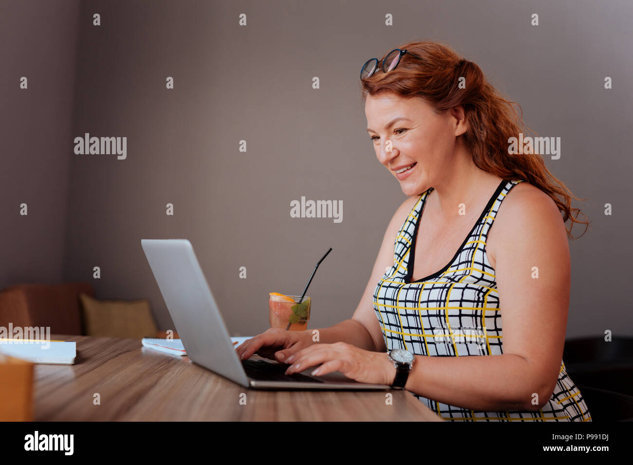 Mature red-haired woman typing important message - Stock Image