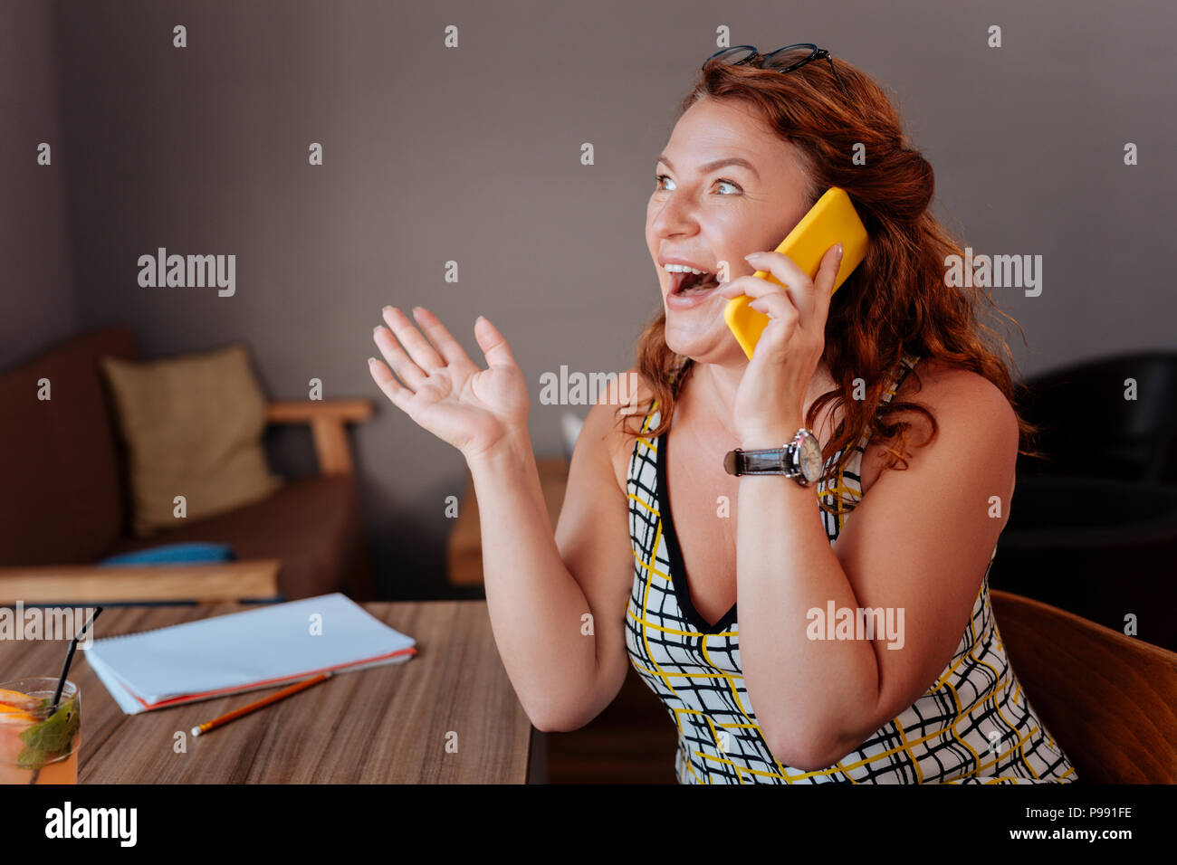 Green-eyed woman feeling surprised while hearing positive news - Stock Image