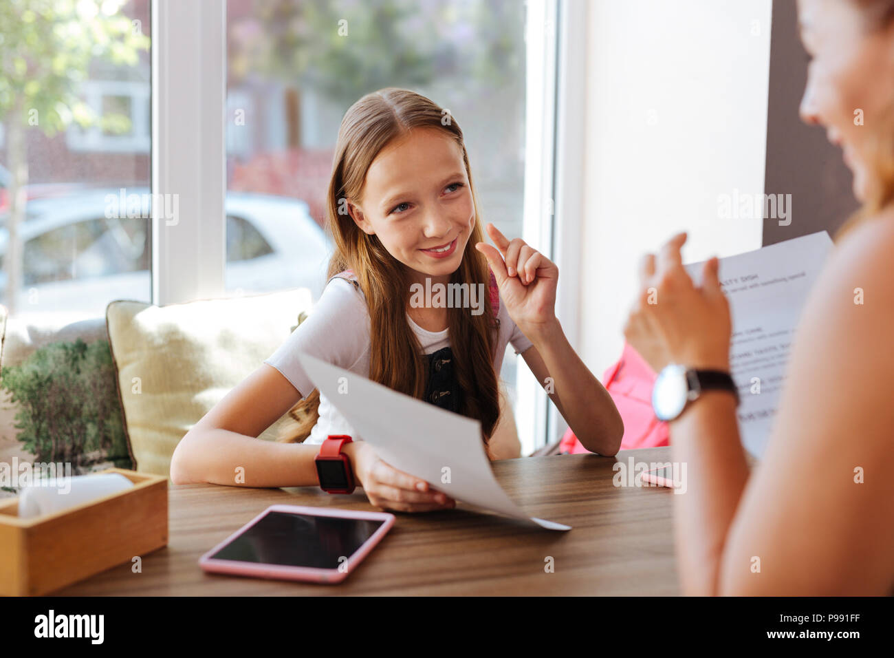 Blonde-haired teenager sitting in cafe with her mother - Stock Image