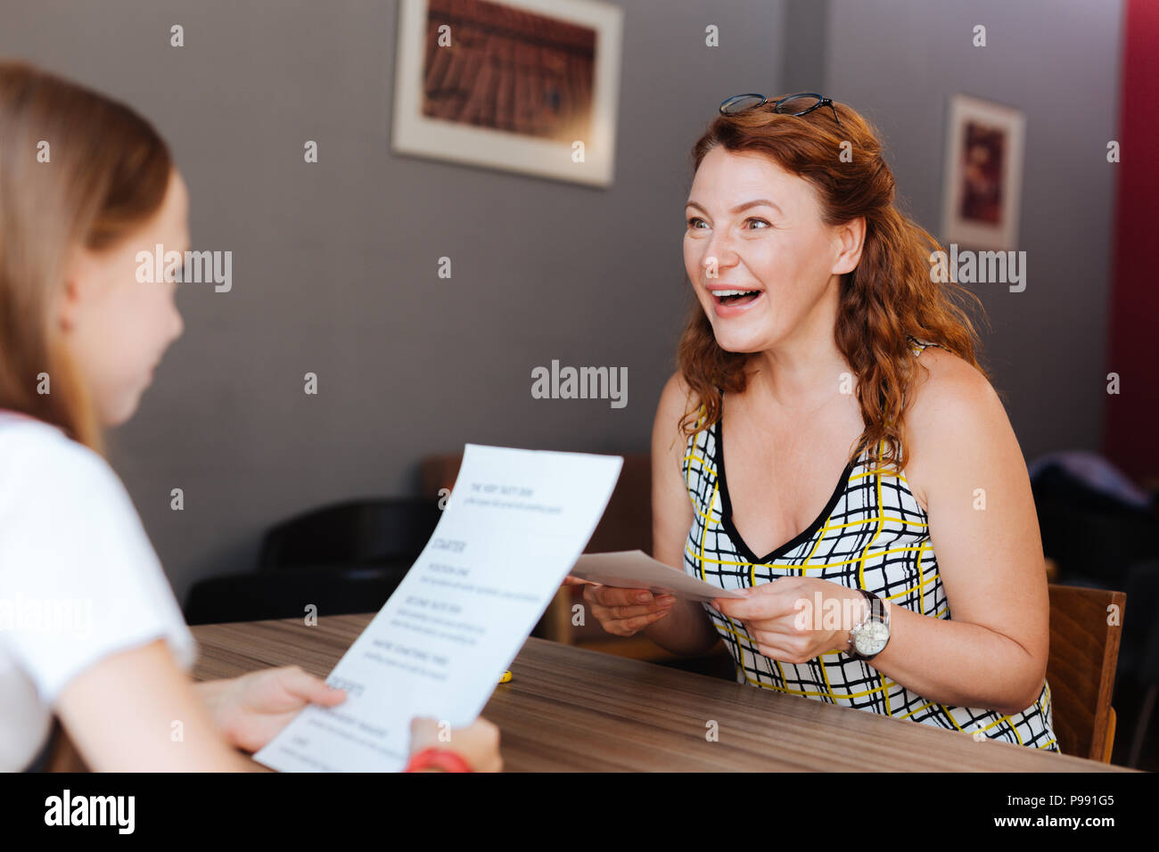 Red-haired mature woman feeling happy spending day with daughter - Stock Image