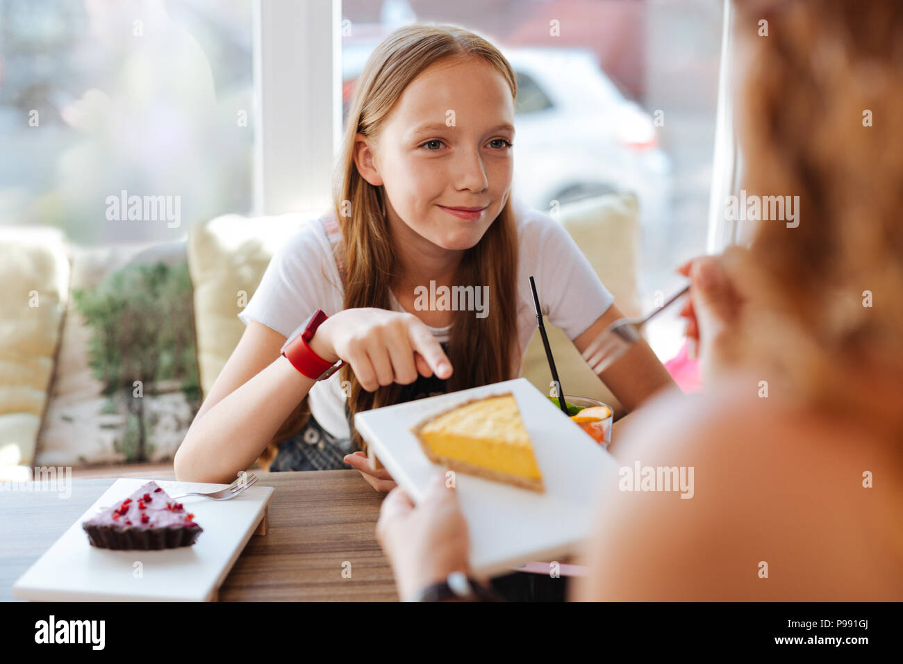 Blonde-haired schoolgirl eating desserts with mother - Stock Image