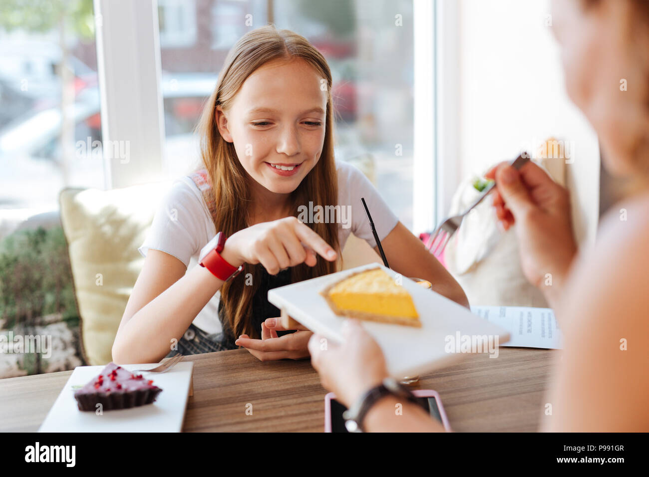 Smiling teenager trying cheesecake with her mother - Stock Image