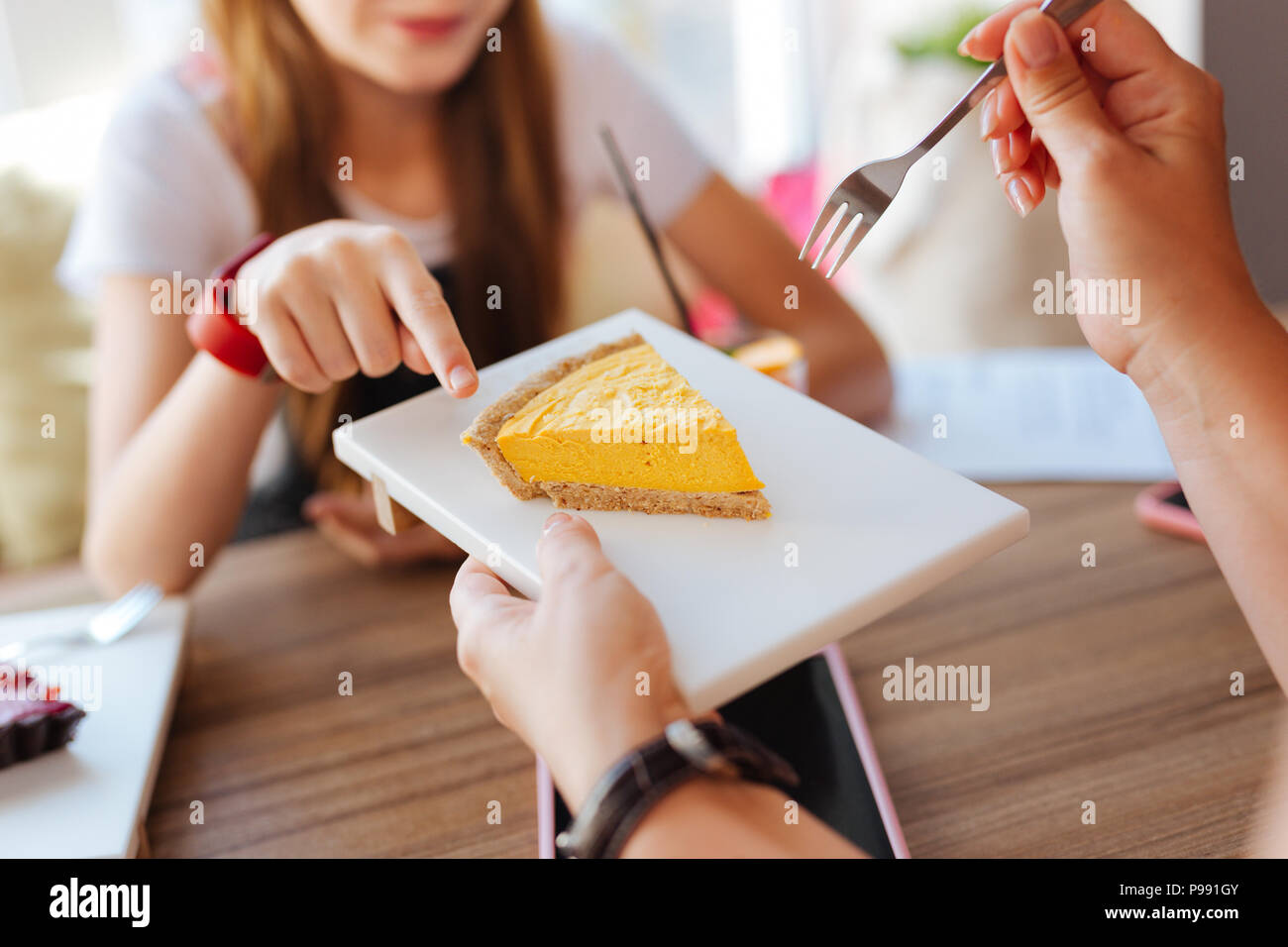 Caring mature woman giving some cheesecake her daughter - Stock Image