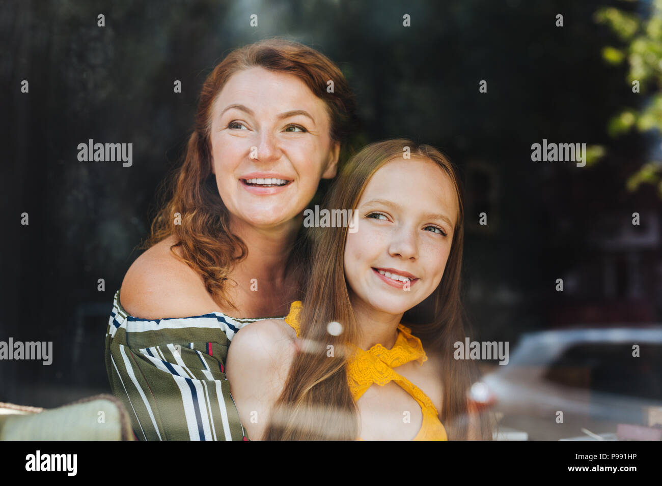 Blonde-haired schoolgirl spending her day with mother - Stock Image