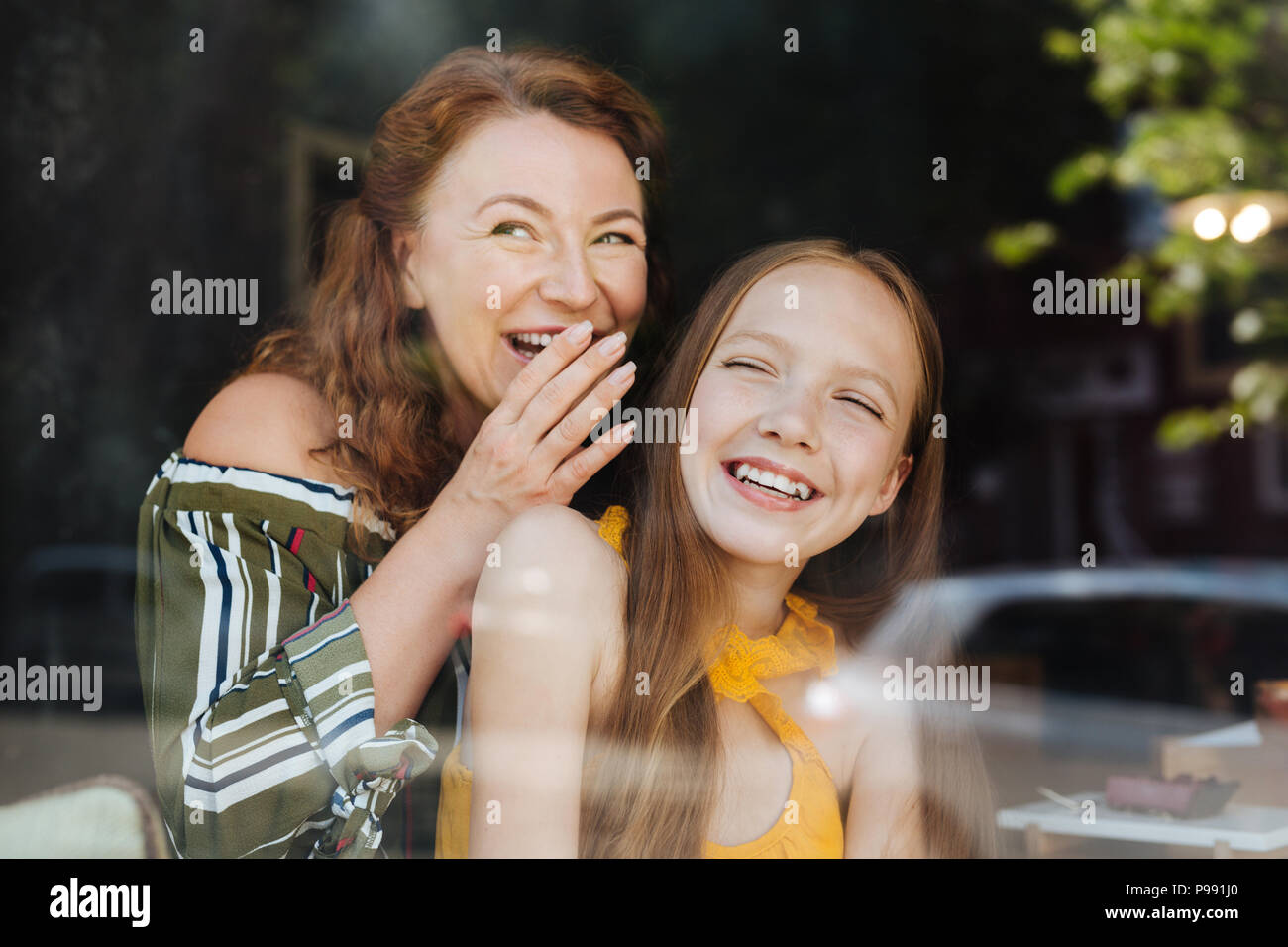 Red-haired woman laughing standing with her daughter - Stock Image