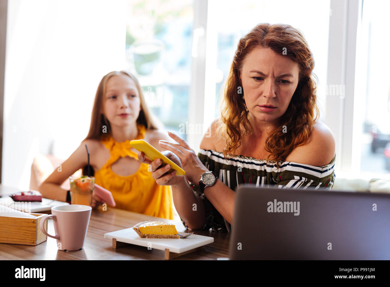 Busy prosperous businesswoman working in cafe - Stock Image