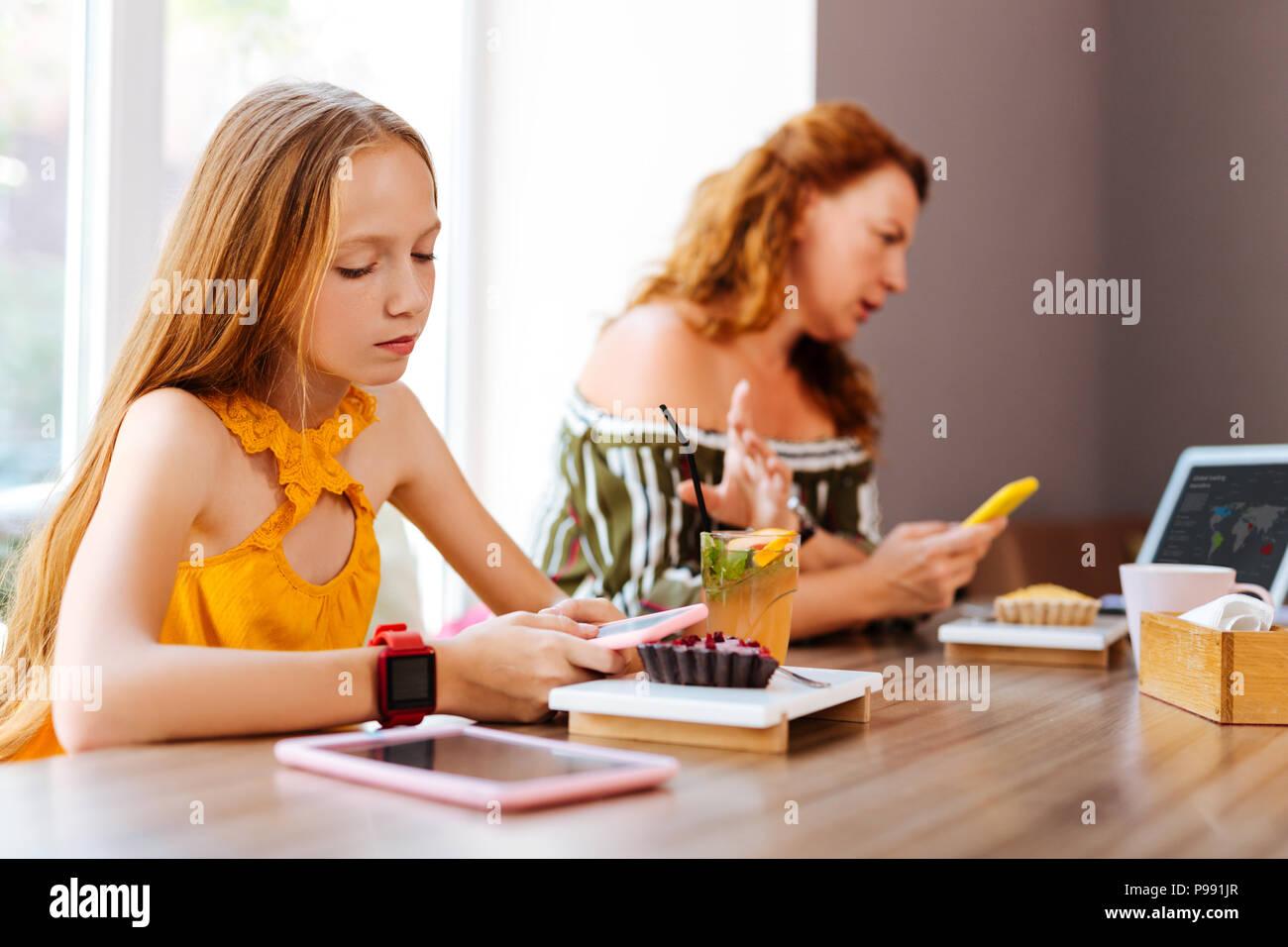 Blonde-haired schoolgirl wearing modern red smart watch - Stock Image