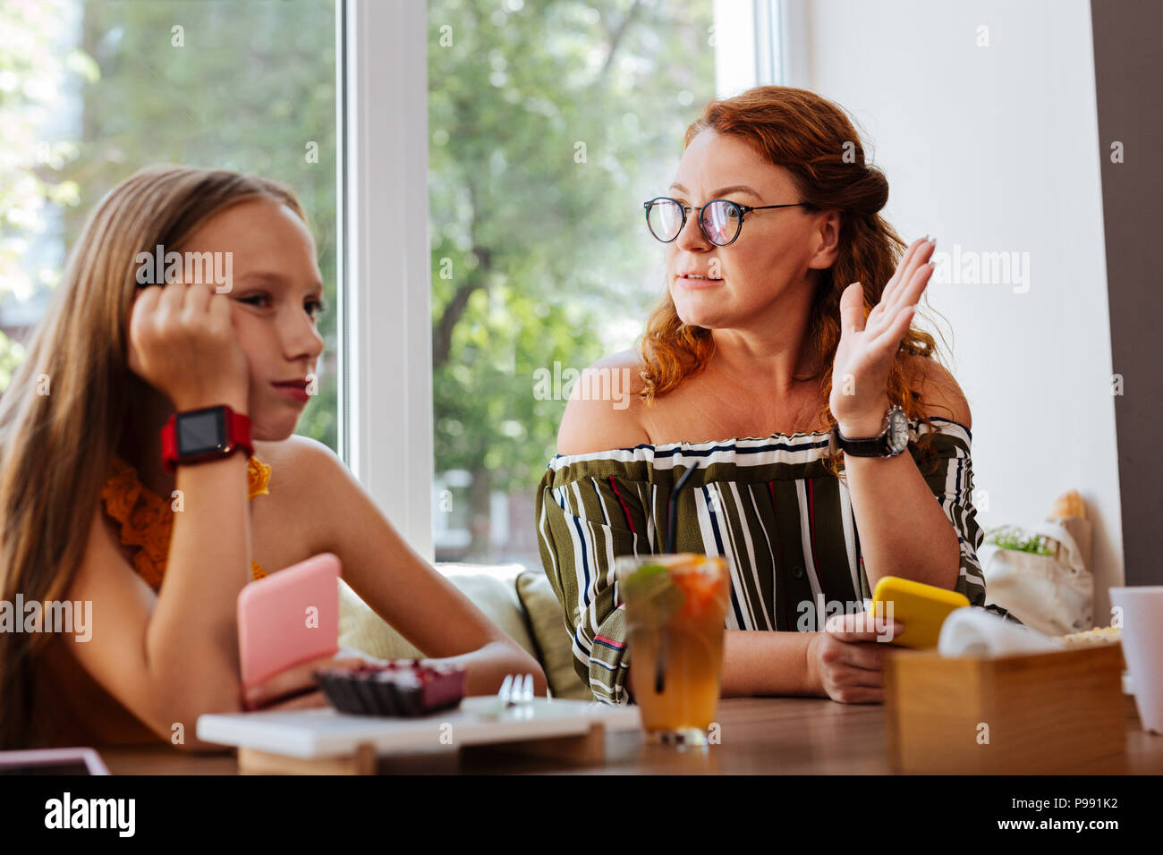 Serious mother wearing glasses having conflict with her daughter - Stock Image