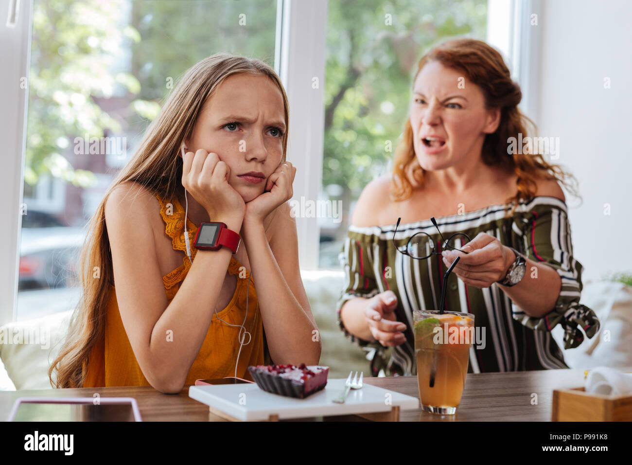 Blue-eyed schoolgirl feeling angry arguing with mother - Stock Image