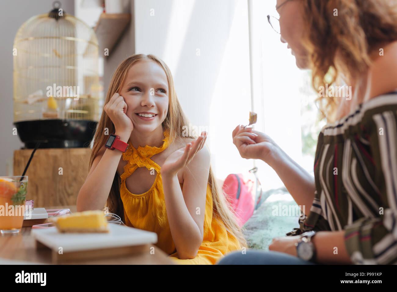 Beaming blonde-haired teenager enjoying talking to her mother - Stock Image
