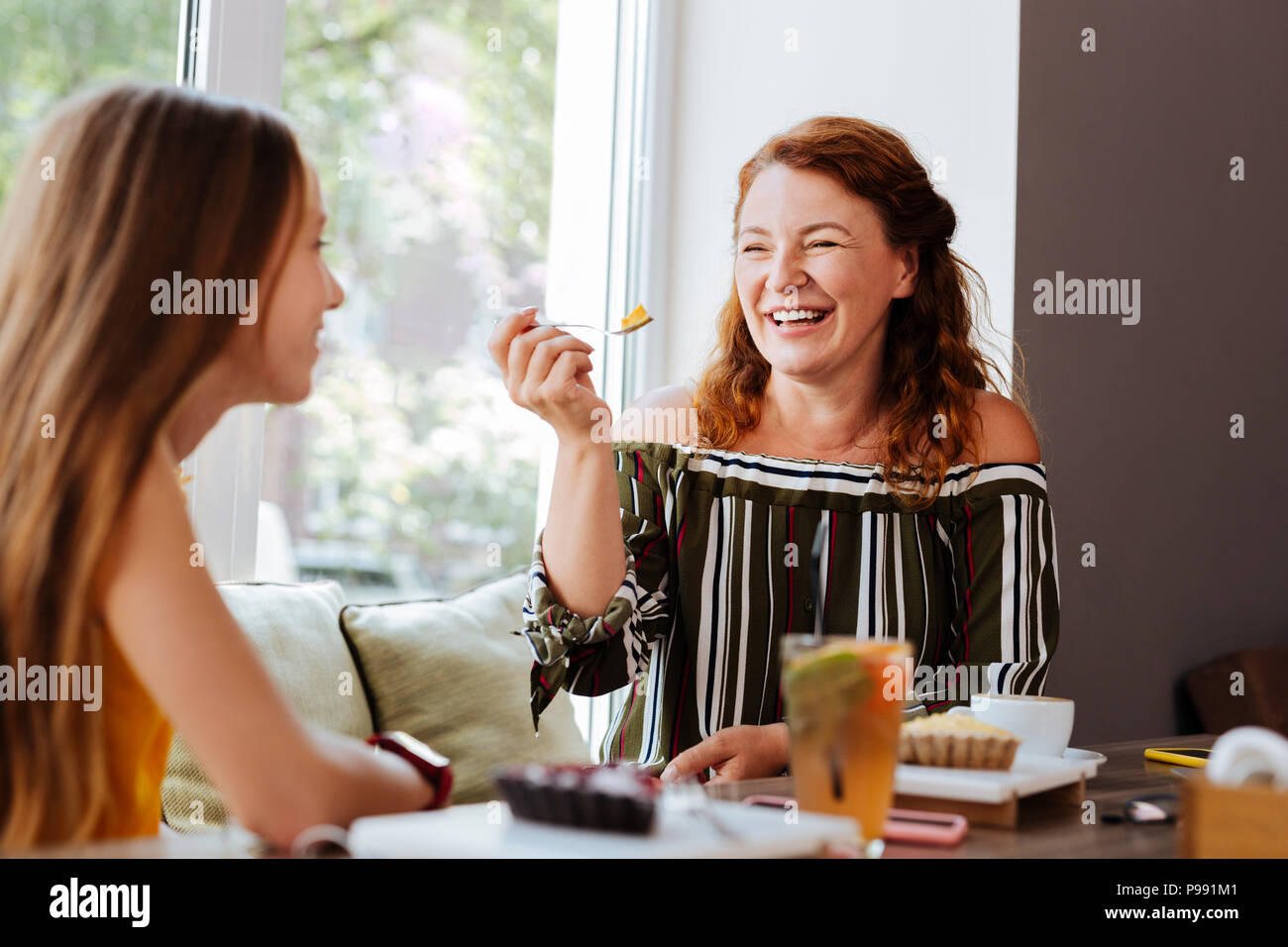 Red-haired woman laughing while talking to daughter - Stock Image