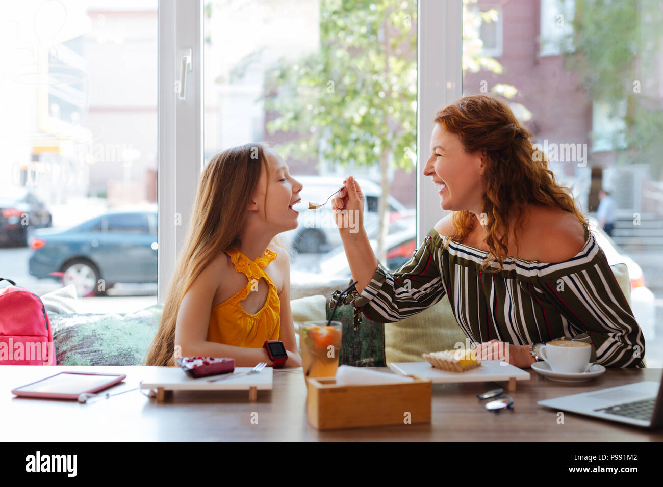 Caring red-haired woman giving piece of cake daughter - Stock Image