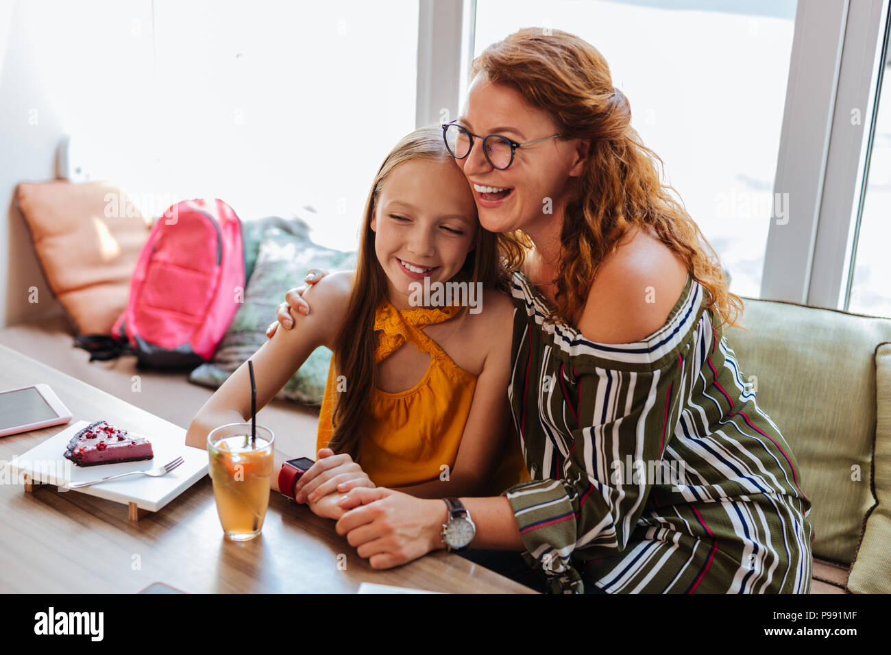 Happy beaming red-haired mother hugging her girl - Stock Image