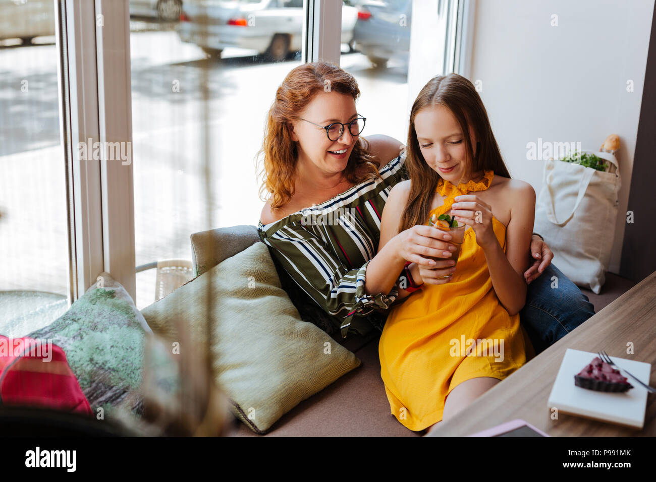 Beautiful teenage girl leaning on her happy mother - Stock Image
