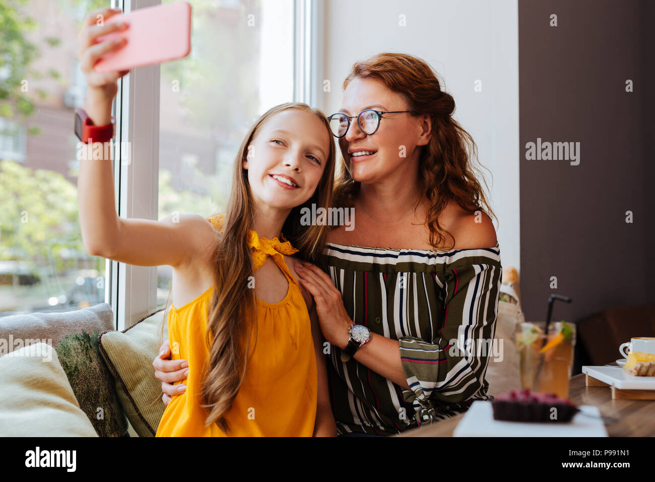 Modern teenage girl making selfie with mother - Stock Image