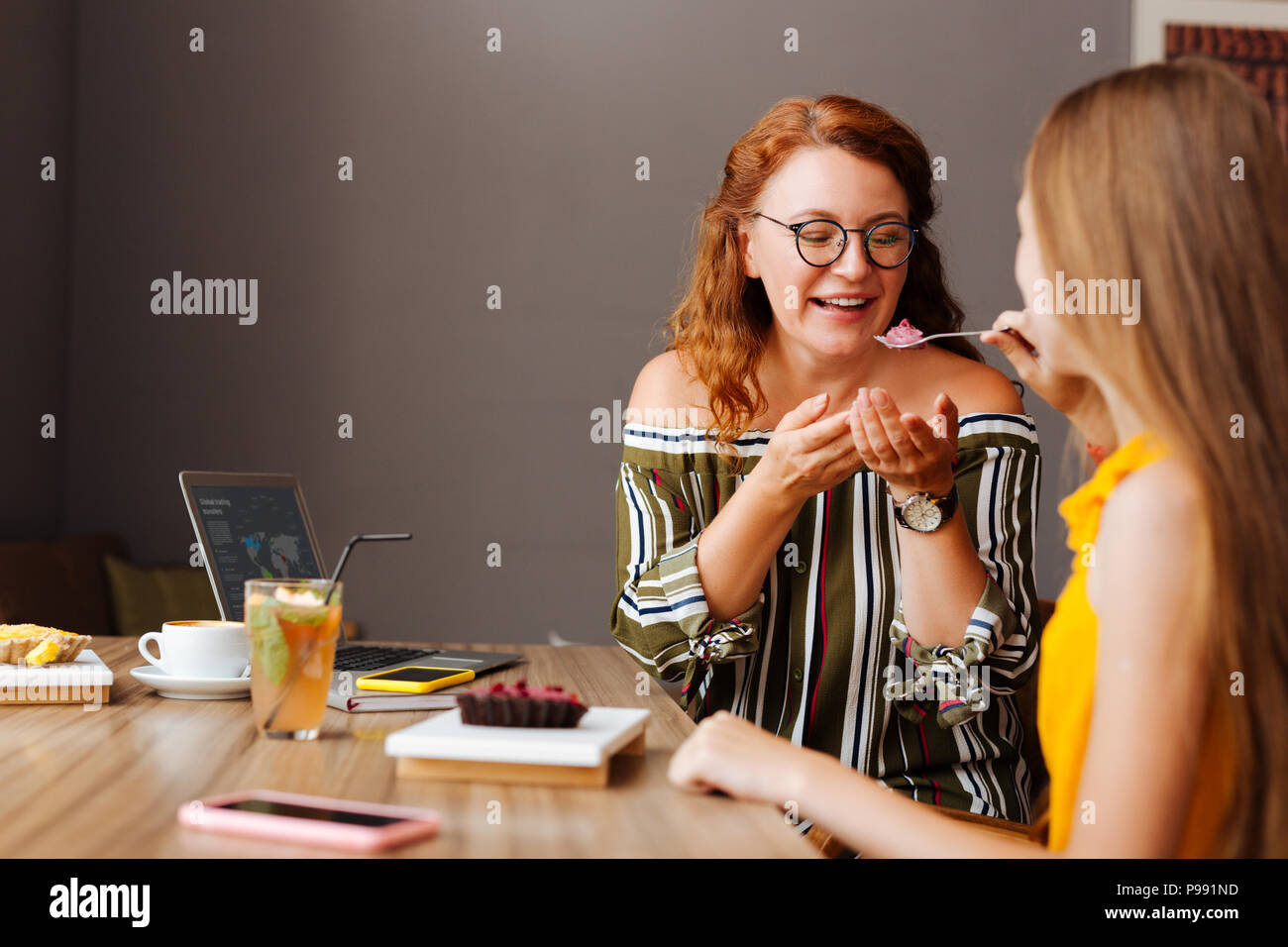 Loving teenage daughter giving piece of dessert her mother - Stock Image