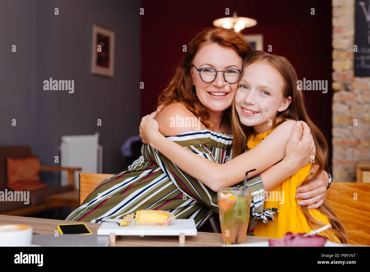 Loving mother and daughter spending their morning in cafe - Stock Image