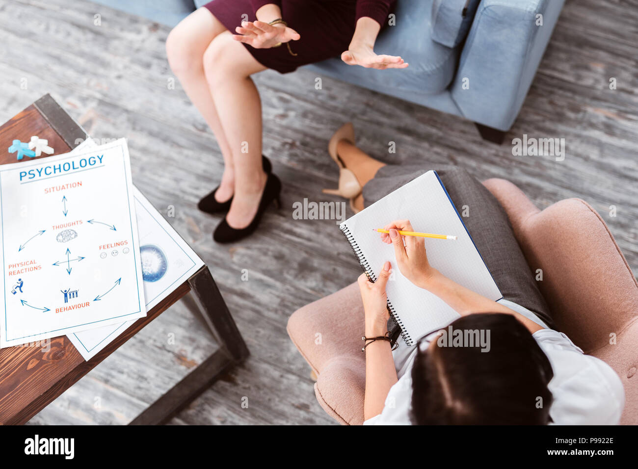 Emotional patient using gestures and a psychologist making notes - Stock Image