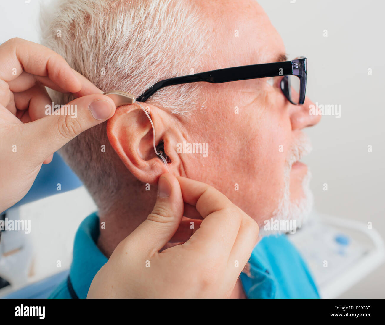 adjusting of a hearing aid for an aged man - Stock Image