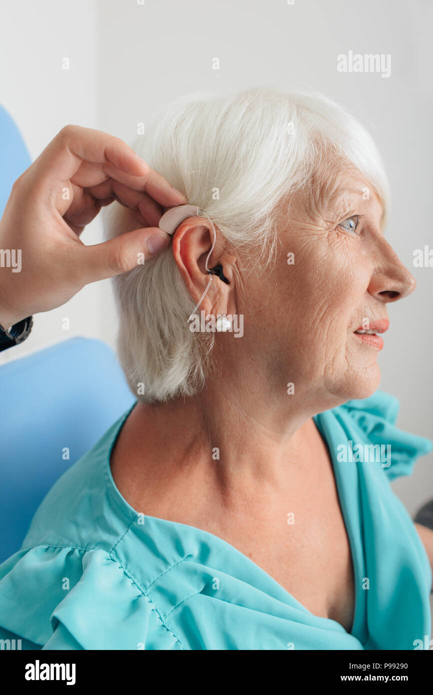 adjusting of a hearing aid for an aged woman - Stock Image
