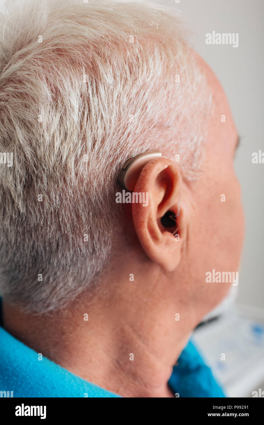 hearing aid on the ear of an elderly patient, close-up - Stock Image