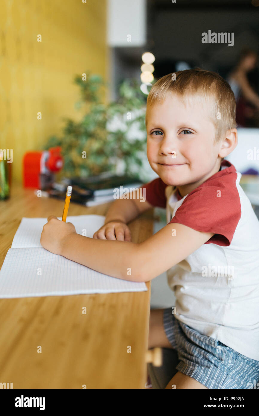 Photo of boy with pen and notebook sitting at table - Stock Image