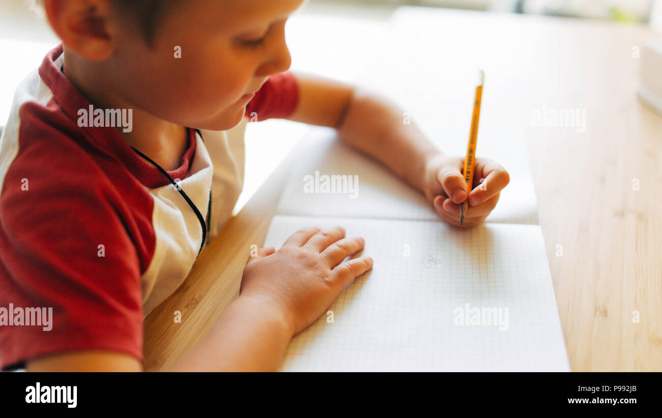 Image of boy with pen and notebook sitting at table - Stock Image