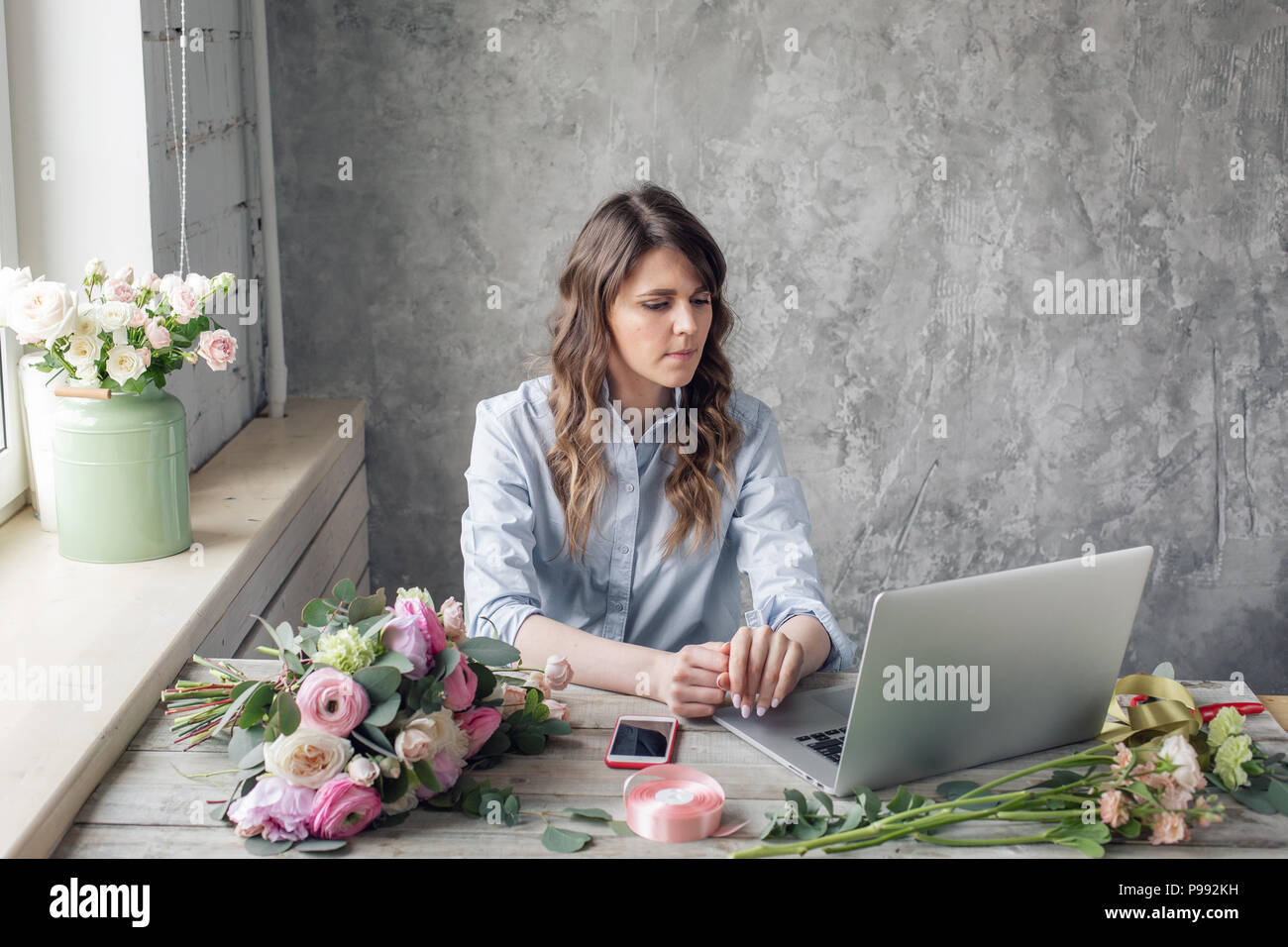 The concept of order-taking and delivery. working table in flower shop. Girl assistant or owner in floral design studio, making decorations and arrangements. - Stock Image