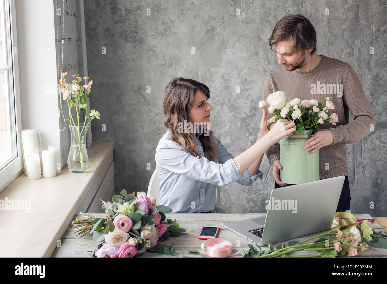 The concept of working in a flower shop. Order-taking and delivery. Woman owner and man assistant in floral design studio, making decorations and arrangements. - Stock Image