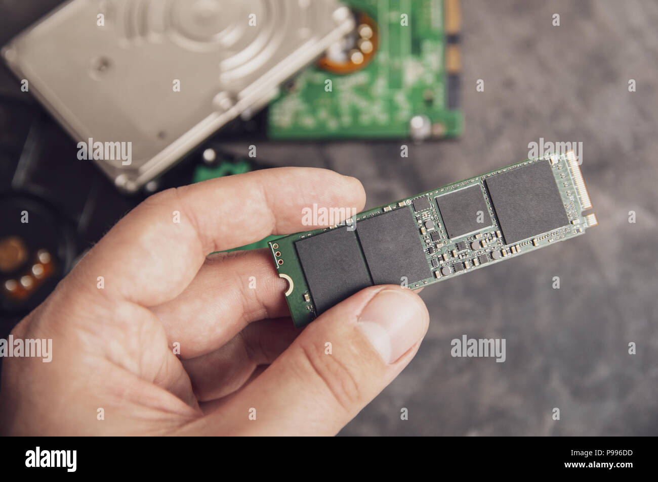 Man's hand holding modern M.2 drive with an old HDD disks in the background - Stock Image
