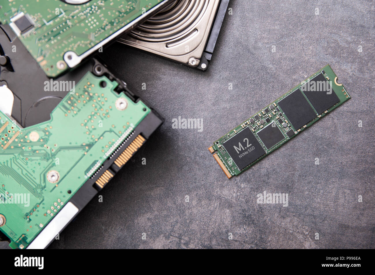 Modern M.2 SSD drive and old hard disk drives lie on a stone slab - Stock Image